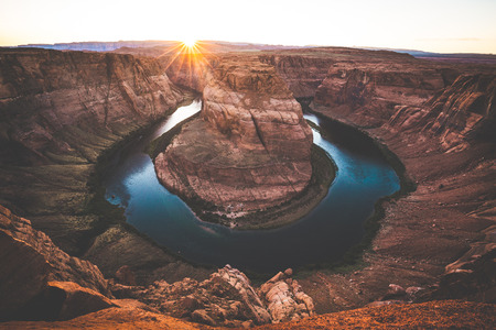 Classic wide-angle view of famous Horseshoe Bend, a horseshoe-shaped meander of the Colorado River located near the town of Page, in beautiful golden evening light at sunset in summer, Arizona, USA Stock Photo