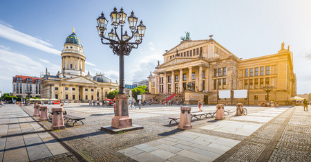Panoramic view of famous Gendarmenmarkt square with Berlin Concert Hall and German Cathedral in golden evening light at sunset with blue sky and clouds in summer, Berlin Mitte district, Germany Standard-Bild