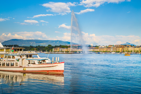 Panoramic view of historic Geneva skyline with famous Jet dEau fountain and ships at harbor district in beautiful evening light at sunset with blue sky and clouds in summer, Canton Geneva, Switzerland Stock Photo