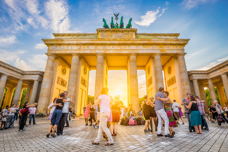 黄金夜の夏、ベルリン、ドイツの青空と夕日の光で有名なブランデンブルク門、平和と団結と歴史的なランドマークのためのシンボルの前で踊る人