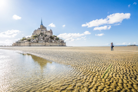 Panoramic view of famous historic Le Mont Saint-Michel tidal island with male tourist taking a photograph on a sunny day with blue sky and clouds in summer, Normandy, northern France Фото со стока