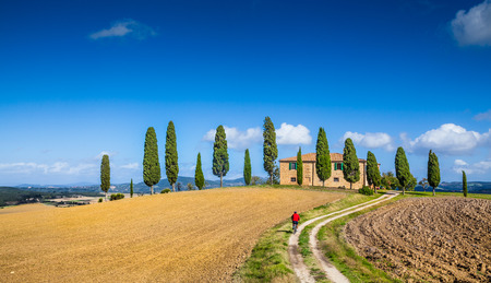 Classic panorama view of scenic Tuscany landscape with famous farmhouse and male cyclist on a country road on a beautiful sunny day with blue sky and clouds in summer, Val d'Orcia, Italy