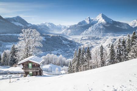 青い空と雲と寒い晴れた日に伝統的な木造シャレーとアルプスの風光明媚な白い冬不思議の国の山の景色のパノラマ ビュー