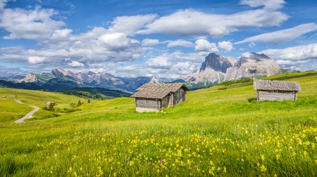 Beautiful view of idyllic alpine mountain scenery with traditional old mountain chalets and fresh green meadows on a sunny day with blue sky and clouds in springtime, Alpe di Siusi, South Tyrol, Italy