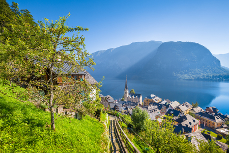 Classic postcard view of famous Hallstatt lakeside town in the Alps with idyllic pathway leading uphill on a beautiful sunny day with blue sky in summer, Salzkammergut region, Austria