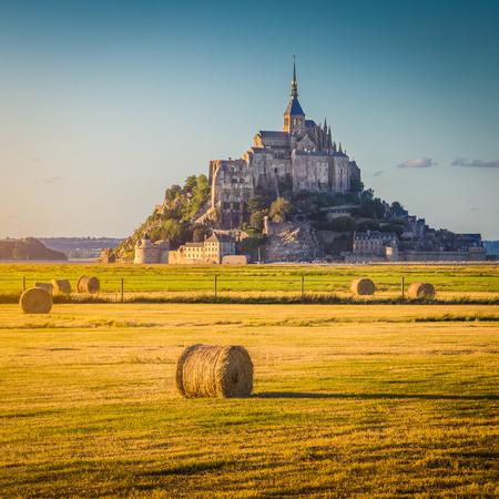 美しい景色の有名な歴史的なモン サンミッ シェル干し草で夏の夕日で黄金夜の光では、ノルマンディー、フランスでレトロなヴィンテージ Instagram スタイル パステル フィルター効果、フィールド上俵します。 写真素材 - 78336520