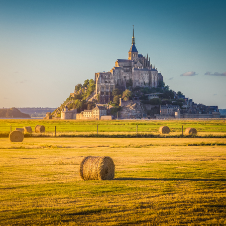 Beautiful view of famous historic Le Mont Saint-Michel in golden evening light at sunset in summer with hay bales on fields with retro vintage  style pastel filter effect, Normandy, France Stock Photo