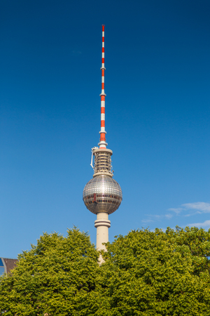 Panoramic vertical view of famous Berlin TV tower at Alexanderplatz on a beautiful sunny day with blue sky and green trees in summer, central Berlin Mitte, Germany Stock Photo