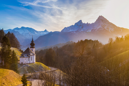 Idyllic mountain scenery in the Alps with pilgrimage church of Maria Gern and famous Watzmann summit in the background in golden evening light at sunset in fall, Berchtesgadener Land, Bavaria, Germany
