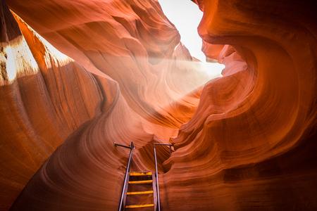 Bela vista de formações de arenito incríveis com uma escada que leva em direção a um feixe de luz mágico no famoso Antelope Canyon, perto da cidade histórica de Page no lago Powell, sudoeste americano, Arizona, EUA. Foto de archivo - 80060411