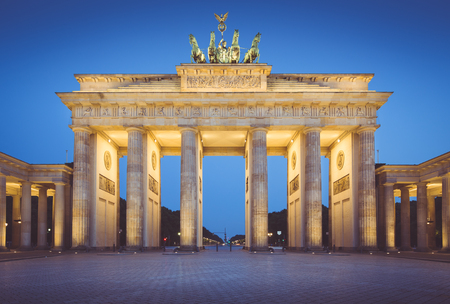 Classic view of famous Brandenburger Tor (Brandenburg Gate), one of the best-known landmarks and national symbols of Germany, during blue hour with retro vintage  VSCO filter, Berlin, Germany