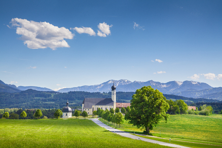 Classic view of famous Wilparting Pilgrimage Church with green meadows and trees on a sunny day with blue sky and clouds in springtime, Irschenberg, Upper Bavaria, Germany