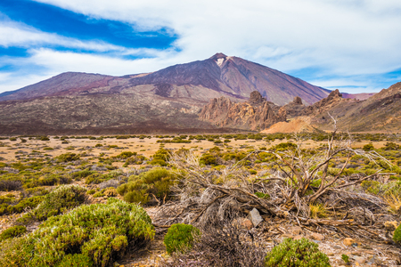 Panoramic view of barren scenery with famous Pico del Teide mountain volcano summit in the background on a beautiful sunny day with clouds, Teide National Park, Tenerife, Canary Islands, Spain