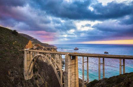 Scenic panoramic view of historic Bixby Creek Bridge along world famous Highway 1 in beautiful evening twilight with dramatic cloudscape during blue hour at dusk, Monterey County, California, USA