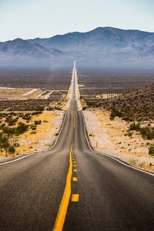 sierra: Classic vertical view of an endless straight road running through the barren scenery of famous Death Valley with extreme heat haze on a beautiful sunny day with blue sky in summer, California, USA Stock Photo