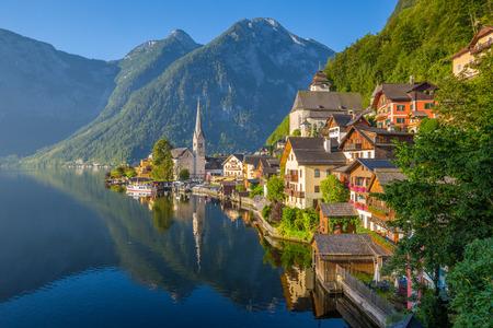 夏、オーストリア ザルツカンマーグート地方の美しい晴れた日に日の出風光明媚な黄金朝の光でアルプスで有名なハルシュタット湖畔の町の古典的