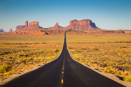Classic panorama view of historic U.S. Route 163 running through famous Monument Valley in beautiful golden evening light at sunset on a beautiful sunny day with blue sky in summer, Utah, USA 免版税图像 - 80060549