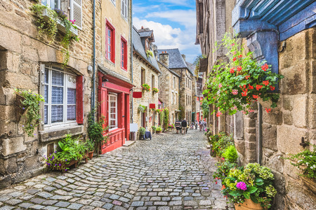 Beautiful view of scenic narrow alley with historic traditional houses and cobbled street in an old town in Europe with blue sky and clouds in summer with retro vintage  grunge filter effect Stock Photo
