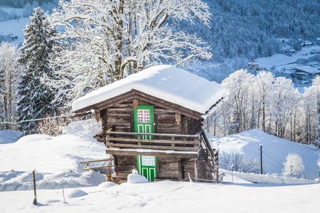 추운 화창한 날에 알프스에서 경치 좋은 하얀 겨울 원더 랜드 산의 경치에 내장 된 전통적인 목조 산 샬레의 아름 다운 경치 스톡 콘텐츠