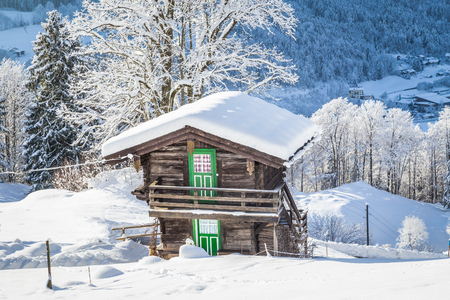 Beautiful view of traditional wooden mountain chalet embedded in scenic white winter wonderland mountain scenery in the Alps on a cold sunny day Stock fotó