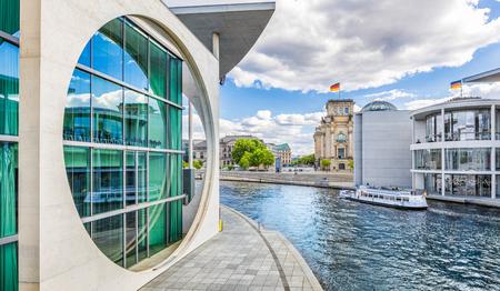Panoramisch zicht op de Berlijnse regeringswijk met excursieboot op de Spree-rivier voorbij het beroemde Reichstag-gebouw en Paul Lobe Haus op een zonnige dag met blauwe lucht en wolken, Berlin Mitte, Duitsland