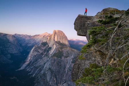 Een onverschrokken wandelaar bevindt zich op een overhangende rots genietend van het uitzicht naar beroemde Halve koepel bij Gletsjerpunt overzie in mooie nazonsondergangschemering, Yosemite Nationaal Park, Californië, de VS Stockfoto