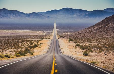 Vista panorâmica clássica de uma estrada reta sem fim que atravessa o cenário árido do sudoeste americano com uma névoa de calor extremo em um lindo dia ensolarado e quente, com céu azul no verão Foto de archivo