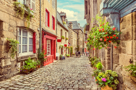 french way: Beautiful view of scenic narrow alley with historic traditional houses and cobbled street in an old town in Europe with blue sky and clouds in summer with retro vintage Instagram grunge filter effect Stock Photo