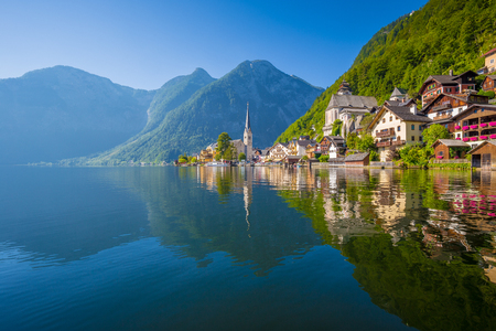 Classic postcard view of famous Hallstatt lakeside town reflecting in Hallstattersee lake in the Austrian Alps in scenic morning light on a beautiful sunny day in summer, Salzkammergut region, Austria