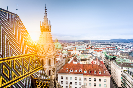 Aerial view over the historical rooftops of Vienna from the north tower of famous St. Stephen's Cathedral in beautiful golden evening light at sunset in summer, central Vienna, Austria Stockfoto