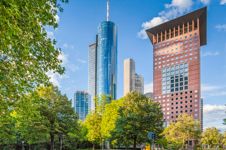 Panoramic view of modern skyscrapers in the financial district of Frankfurt am Main with green trees in public park on a beautiful sunny day with blue sky and clouds in summer, Germany Stock Photo