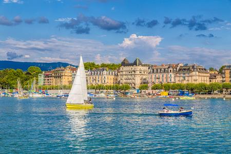夏の青空と雲と夕暮れ時の美しい夕暮れ時の港でジュネーブ湖のボートとジュネーブの歴史的な市内中心部の美しい景色, ジュネーブ, スイス 報道画像