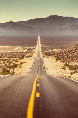 Classic vertical view of an endless straight road running through the barren scenery of famous Death Valley with extreme heat haze on a beautiful sunny day with blue sky in summer, California, USA Stock Photo