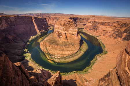 Classic wide-angle view of famous Horseshoe Bend, a horseshoe-shaped meander of the Colorado River, on a beautiful sunny day with blue sky and clouds in summer, Page, Arizona, USA