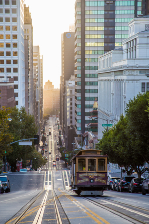 Classic view of historic Cable Car riding on famous California Street in beautiful golden morning light at sunrise in summer, San Francisco, California, USA Stock Photo