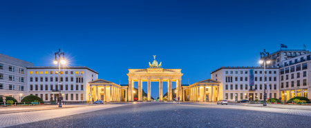 Panoramic view of Pariser Platz with famous Brandenburger Tor (Brandenburg Gate), one of the best-known landmarks and national symbols of Germany, in twilight during blue hour at dawn, Berlin, Germany Фото со стока