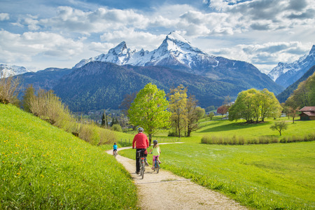 Beautiful view of a group of bikers cycling on a scenic trail in idyllic alpine mountain scenery with fresh green meadows on a beautiful sunny day with blue sky and clouds in springtime