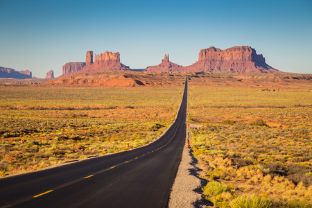 Classic panorama view of historic U.S. Route 163 running through famous Monument Valley in beautiful golden evening light at sunset on a beautiful sunny day with blue sky in summer, Utah, USA