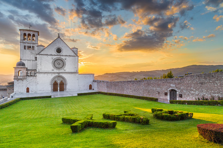 Classic view of famous Basilica of St. Francis of Assisi (Basilica Papale di San Francesco) with pax sign in beautiful golden evening light with dramatic clouds in the sky at sunset, Assisi, Umbria, Italy Stock Photo