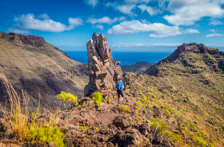 Beautiful view of male tourist hiking in idyllic exotic scenery with the Atlantic Ocean in the  background on a scenic sunny day with blue sky and clouds in summer, Canary Islands, Spain