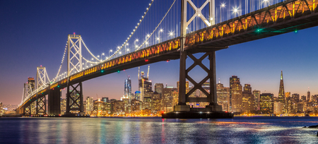 Classic panoramic view of famous Oakland Bay Bridge with the skyline of San Francisco illuminated in beautiful twilight after sunset in summer, California, USA 免版税图像 - 94490097