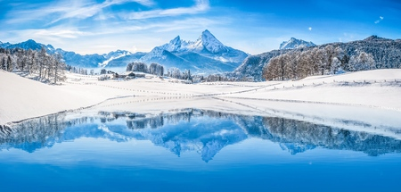 Panoramic view of beautiful white winter wonderland scenery in the Alps with snowy mountain summits reflecting in crystal clear mountain lake on a cold sunny day with blue sky and clouds Фото со стока - 94490101