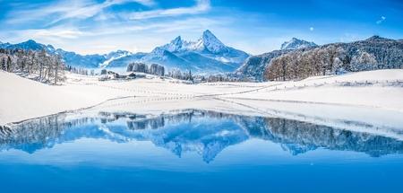 Panoramisch uitzicht op prachtige witte winter wonderland landschap in de Alpen met besneeuwde bergtoppen weerspiegelt in kristalhelder bergmeer op een koude zonnige dag met blauwe lucht en wolken