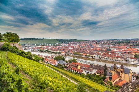 夏の曇りの日、フランコニアの地域、バイエルン州北部、ドイツの曇りの日に美しい夕暮れ時に牧歌的なブドウ園とヴュルツブルクの歴史的な都市
