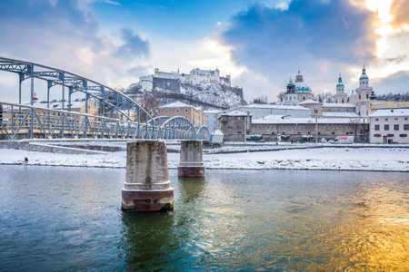 Panoramic view of the famous old town of Salzburg with historic Mozartsteg crossing Salzach river in beautiful golden evening light at sunset with clouds in winter, Salzburg Land, Austria