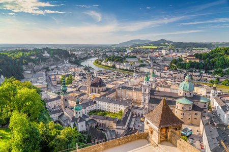 Aerial panoramic view of the historic city of Salzburg with Salzach river in beautiful golden evening light with blue sky and clouds at sunset in summer, Salzburger Land, Austria 스톡 콘텐츠