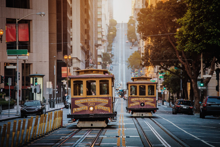 Classic view of historic traditional Cable Cars riding on famous California Street in beautiful early morning light at sunrise in summer with retro vintage style cross processing filter effect, San Francisco, California, USA 新聞圖片