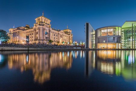 Panoramic view of modern Berlin government district with famous Reichstag building and Spree river illuminated in beautiful post sunset twilight during blue hour at dusk, central Berlin Mitte, Germany Stock Photo
