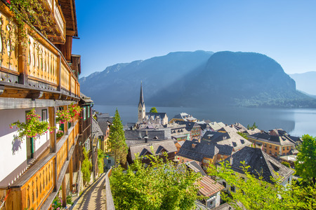 Classic aerial view of famous Hallstatt lakeside town in the Alps with idyllic pathway on a beautiful sunny day with blue sky in summer, Salzkammergut region, Austria