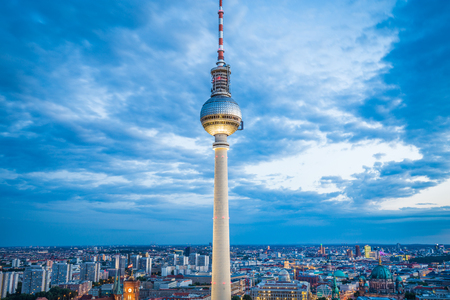 Aerial view of famous TV tower at Alexanderplatz with dramatic cloudscape in twilight during blue hour at dusk, Germany